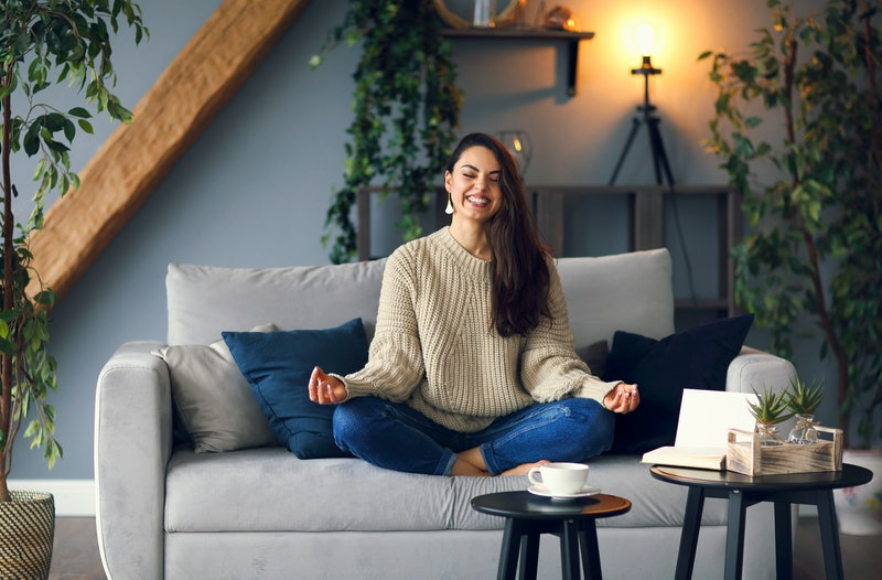 Body and spirit health. Cute smiling woman is learing yoga at home sitting on the sofa