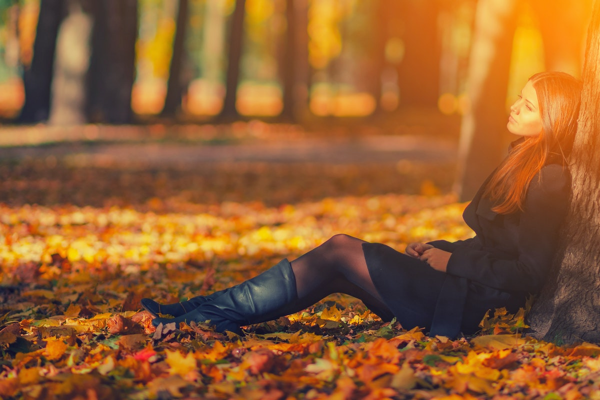 Beautiful woman in black coat and leather boots sitting under tree in autumn park with fallen leaves. Bright young long haired brunette girl relax in park with red yellow maple leaves in fall season