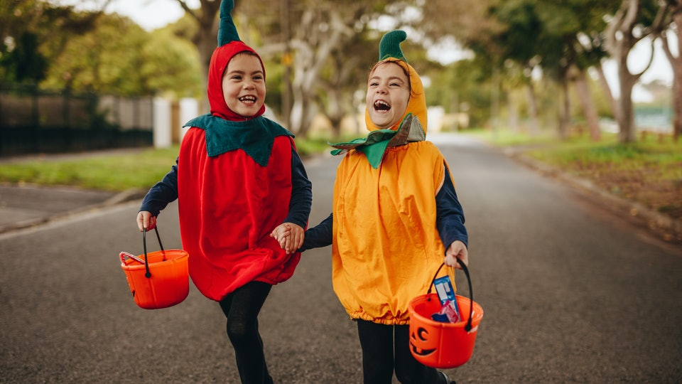 Happy kids in halloween costume trick or treating outdoors. Two little girls in halloween costume with buckets walking outdoors on the street.