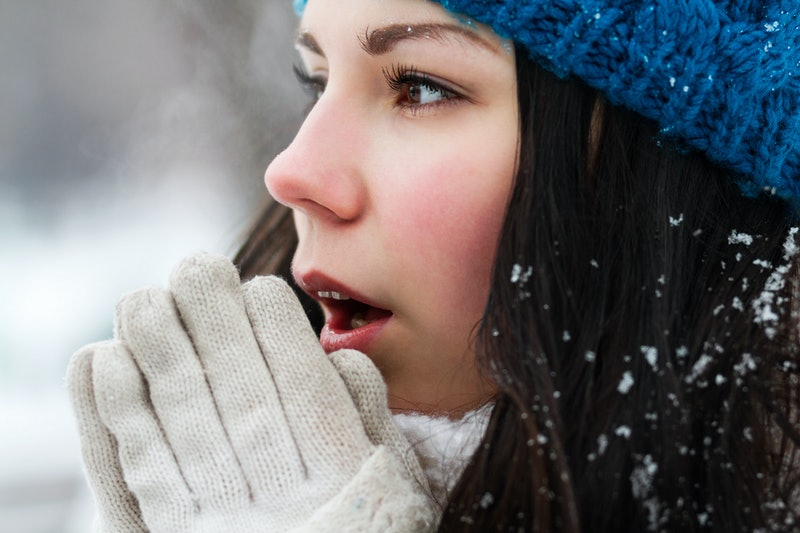 Girl feels cold outside.Portrait of frozen white brunette female in knit blue hat.Young woman breathes warm air on frozen hands.Pretty young model outside in snowy winter day.Cute millenial female