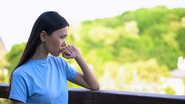 Worried young woman thinking problem standing outdoors house backyard, anxiety