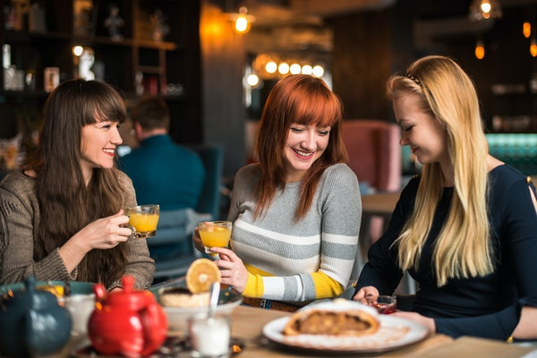 Three friends, happy smile, a festive dinner, where to celebrate, in a restaurant, cafe, desserts tea, coffee, friendly gatherings, jokes, joy, blonde, brunette and redhead girls