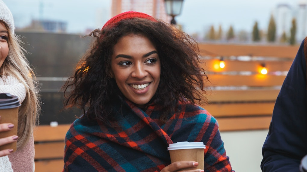 Image of a happy young girl drinking coffee outdoors winter concept.