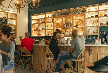 Smiling young African American couple sitting at the counter of a bar talking and having drinks whil...