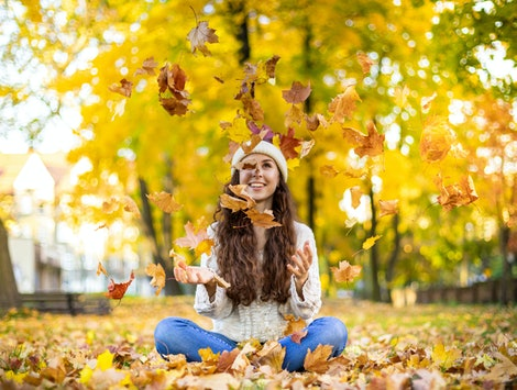 Happy young woman throwing autumn leaves and smiling on colorful nature city background