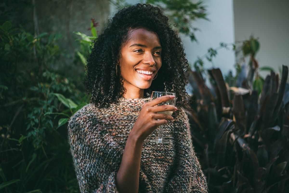 A woman in a comfy sweater smiles and holds a glass of wine outside.