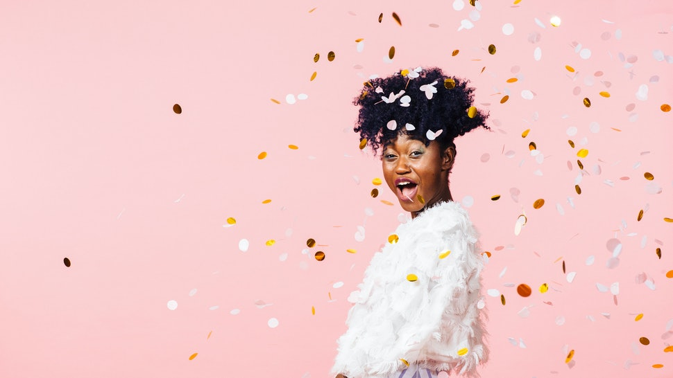 Excited young girl having fun throwing confetti