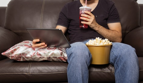 Single man watches movie on digital tablet. They are drinking juice and eating popcorn. Sitting on the sofa in the living room.