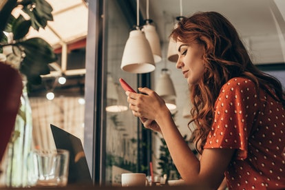 side view of young woman using smartphone at table with laptop in coffee shop