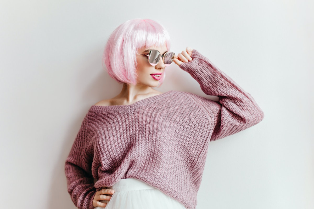 Confident girl with light-pink hair touching her glasses with smile. Indoor photo of good-looking yo...
