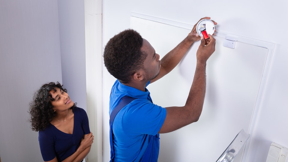 Repairman Changing Battery In Smoke Detector On Wall At Home