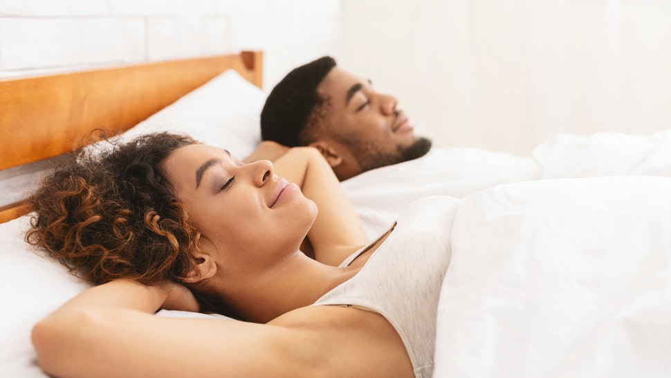 Comfortable sleep position. African american couple sleeping in bed with hands behind heads, free space
