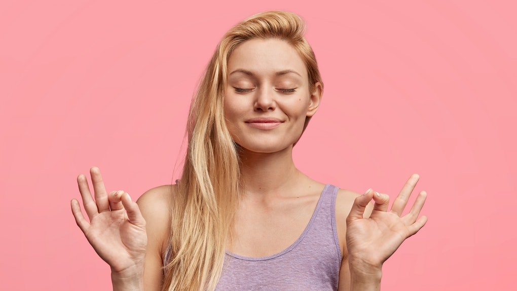 People, calmness concept. Adorable relaxed young female keeps eyes closed and fingers crossed, hopes for something with great desire, poses alone against pink background, shows wishing gesture
