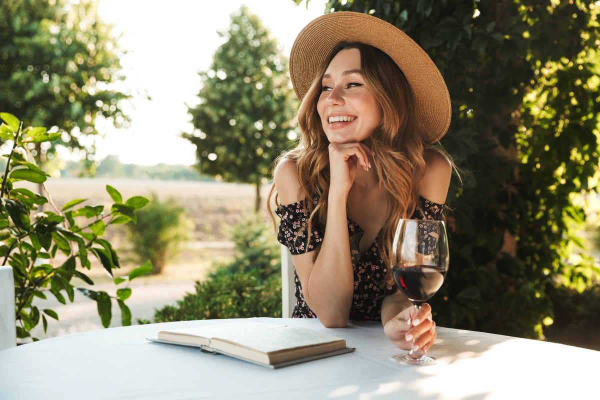 A woman on vacation sits at a table outdoors at a vineyard with a book and holding a glass of red wine.