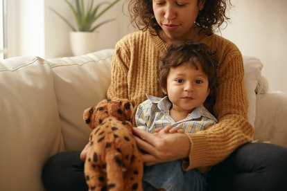 Indoor shot of happy caring young Latin woman sitting on sofa with adorable toddler on her lap playi...