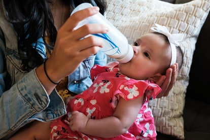 Baby being fed from a bottle.