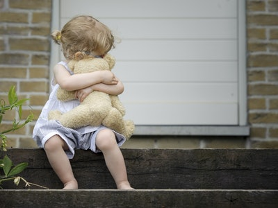 little girl seated on old wooden stairs with teddy bear