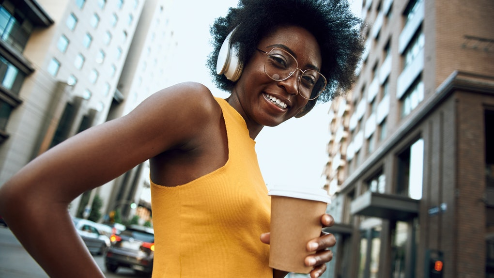 Waist up portrait of smiling woman with headphones holding coffee while walking on the street and listening the music