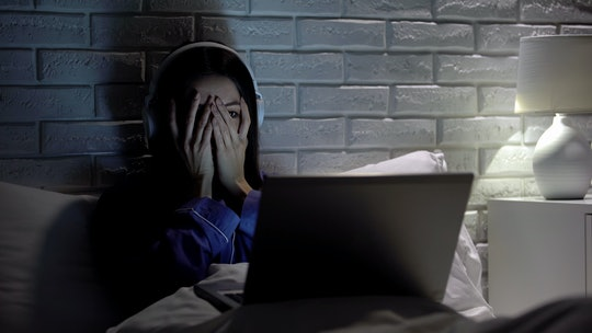 Young female watching scary movie, hiding face in fear, online film service