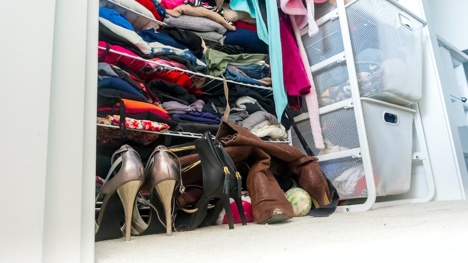 Real apartment closet organized and filled with woman's clothes, depicting shopping, lifestyle habits, real life and clothing choices of a fashionable person.
