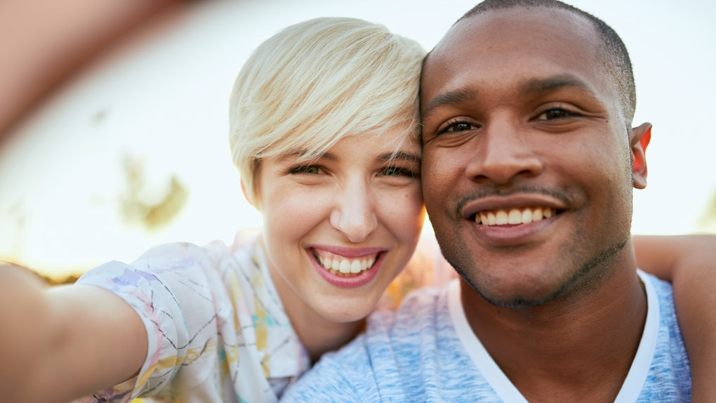 Mixed race couple of millennial in a grass field taking a selfie with a smartphone