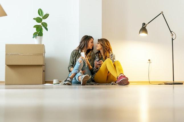 Lesbian couple making a new arrangement in apartment