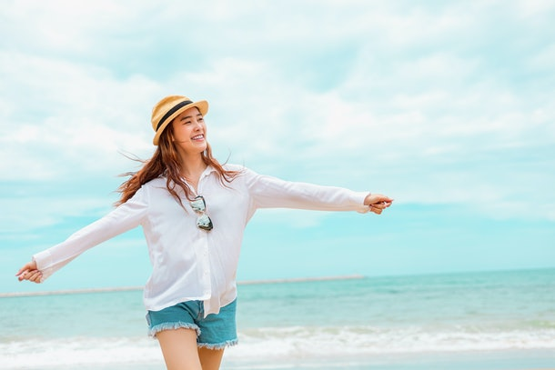 Happy Woman in summer vacation wearing hat and dress enjoying the view at the island beach.