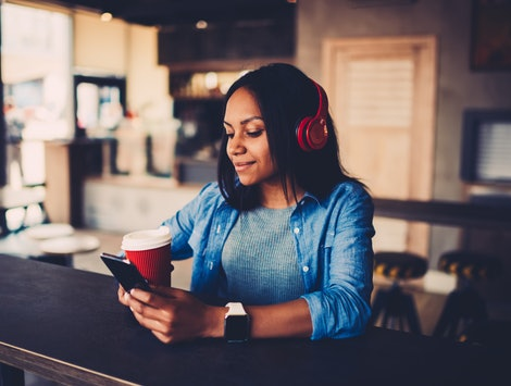 Afro american hipster girl chatting online in social networks with friends and making payment online on internet website listening favourite audio song from own playlist sitting with coffee in cafe