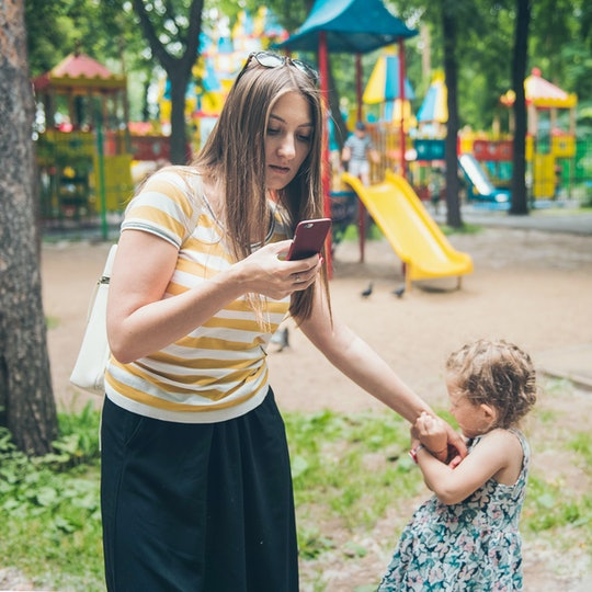 Little  girl pulling hand of her mother  because her mom surfing Internet on smartphone. Gadgets problems. Parents problems.