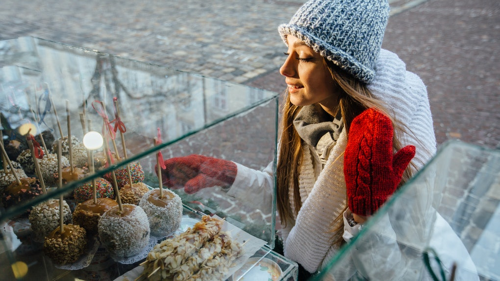 Smiling blond woman is curious looking at the apple candies on the other side of the window, she is thinking about which one looks the most delicious at Christmas market. Enjoy winter holiday mood.