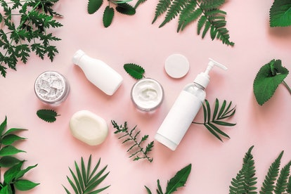 Natural cosmetics and green leaves on pink background, top view, flat lay. Natural organic skincare, bio research and healthy lifestyle concept.
