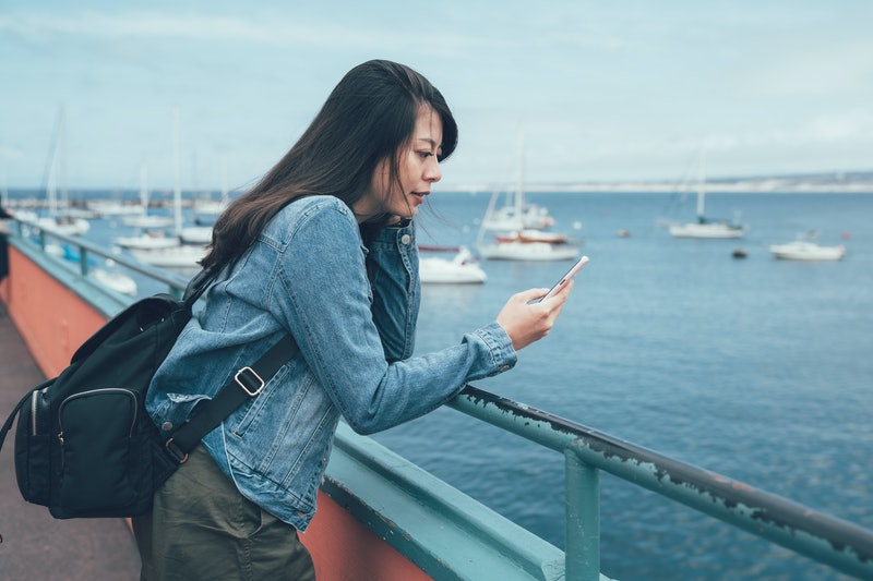 young local asian lady holding cellphone waiting for date in afternoon at beach bay. girl with backpack communicate friends chat on mobile phone seeing ocean boat view Old Fisherman's Wharf.