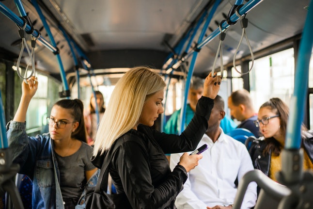 Woman with phone at the public transport