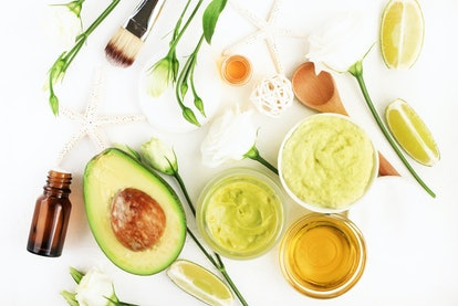Homemade cosmetic mask with fresh avocado & green lime slices fruits, ingredients on white desktop, jars with essential oil and honey, skincare & hair treatment.