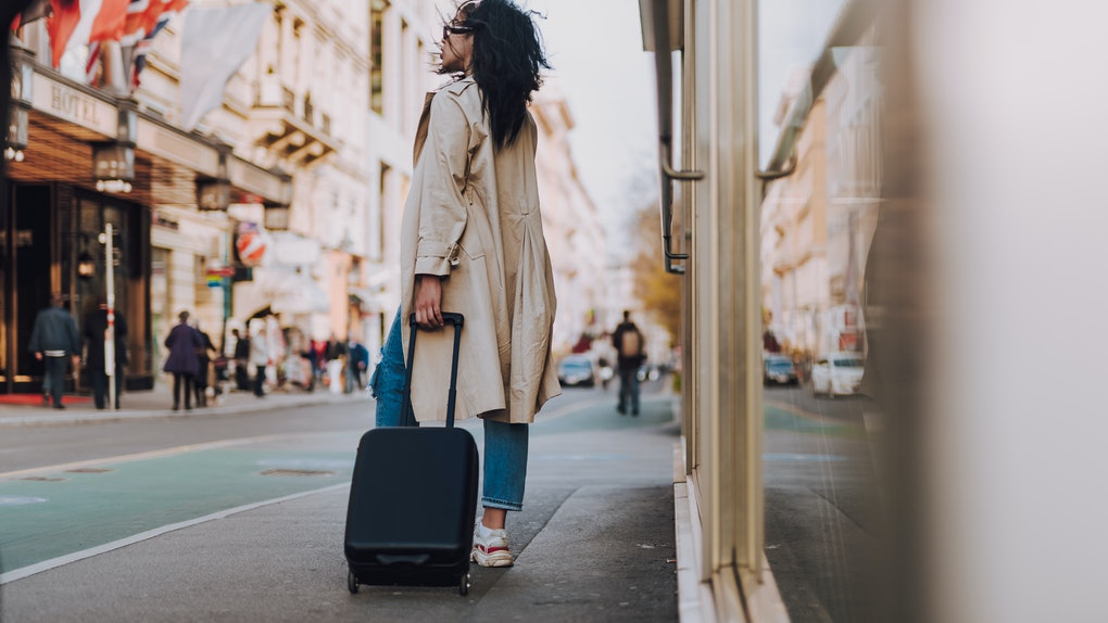 Full length portrait of beautiful young lady in elegant trench coat holding handle of black travel suitcase and looking away