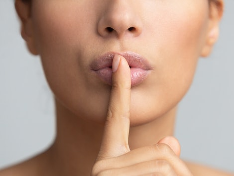 Women's secret. Woman holding finger on lips over grey background