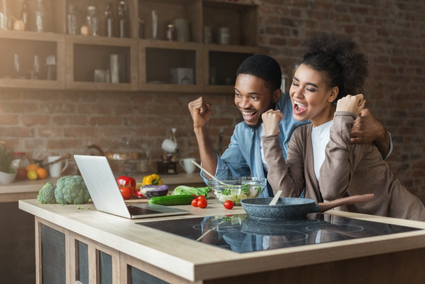 Happy black couple win near laptop while cooking at kitchen