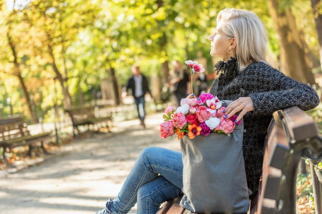 Portrait of young blonde dreamy woman with bouquet of flowers in backpack sits on the bench, side view. Spring concept