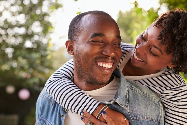 Smiling young black couple piggyback in garden, eyes closed