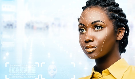 Close up portrait of attractive young african woman showing conceptual face recognition safety scan.