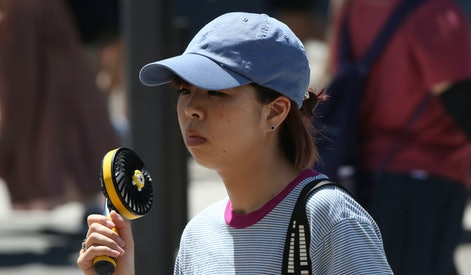 A woman holds a portable fan to avoid the heat in Tokyo, . The mercury is expected to reach 35 degrees Celsius (95 degrees Fahrenheit) on Monday in Tokyo