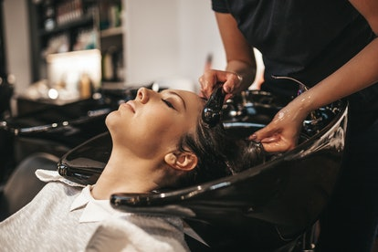 Beautiful young woman getting a hair wash. Hair salon styling concept.