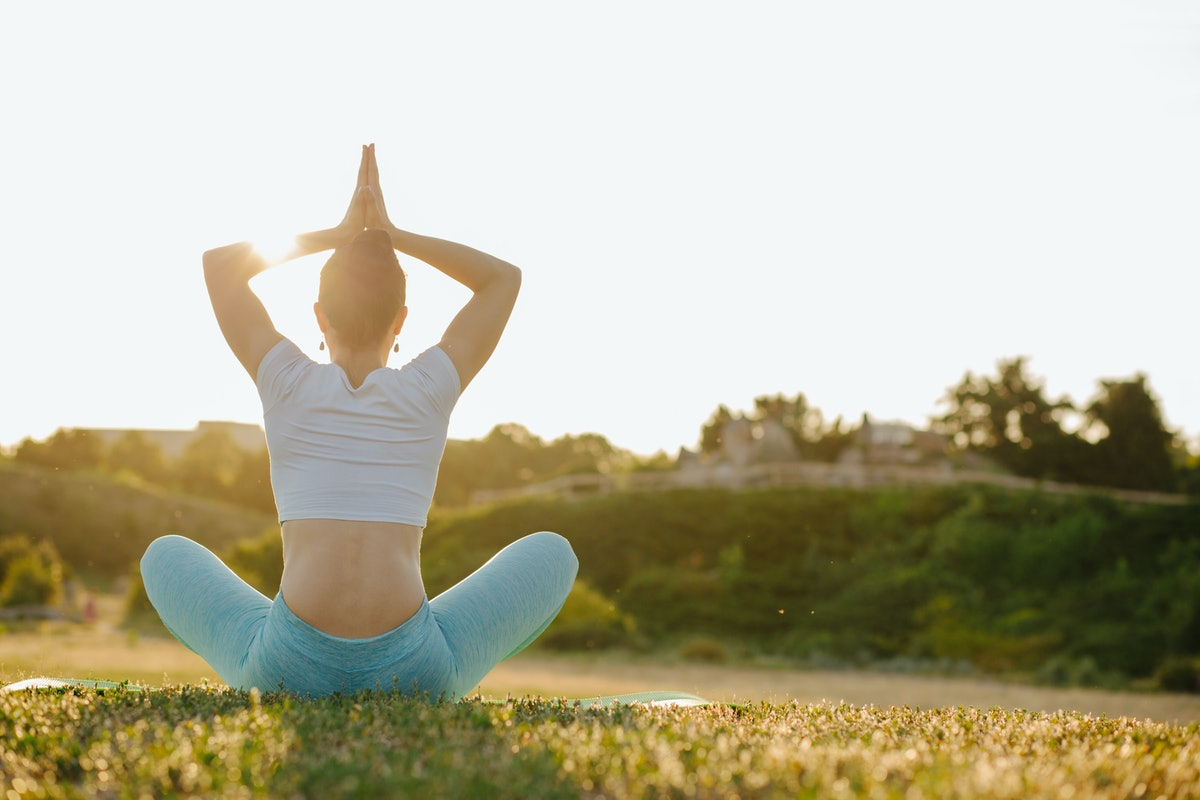 Splendid brunette woman relaxing in nature and practicing yoga in rays of sun. Empty space
