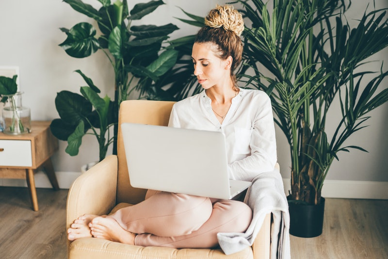 Happy girl sitting on armchair with laptop. Young successful woman working from home.