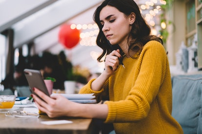 Side view of thoughtful young woman with brown hair and smartphone in yellow sweater touching chin while sitting at desk with notebook in cafe