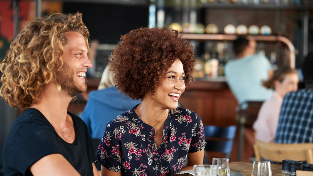 Couple On Date Meeting For Drinks And Food In Restaurant