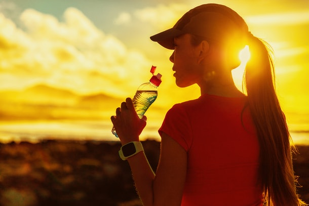 Fitness woman drinking water from sports bottle on afternoon workout after run training jogging outdoors at sunset. Girl wearing running cap silhouette against sun flare.