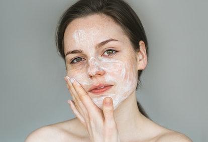 Woman soap face. Beautiful young girl washing her face.
