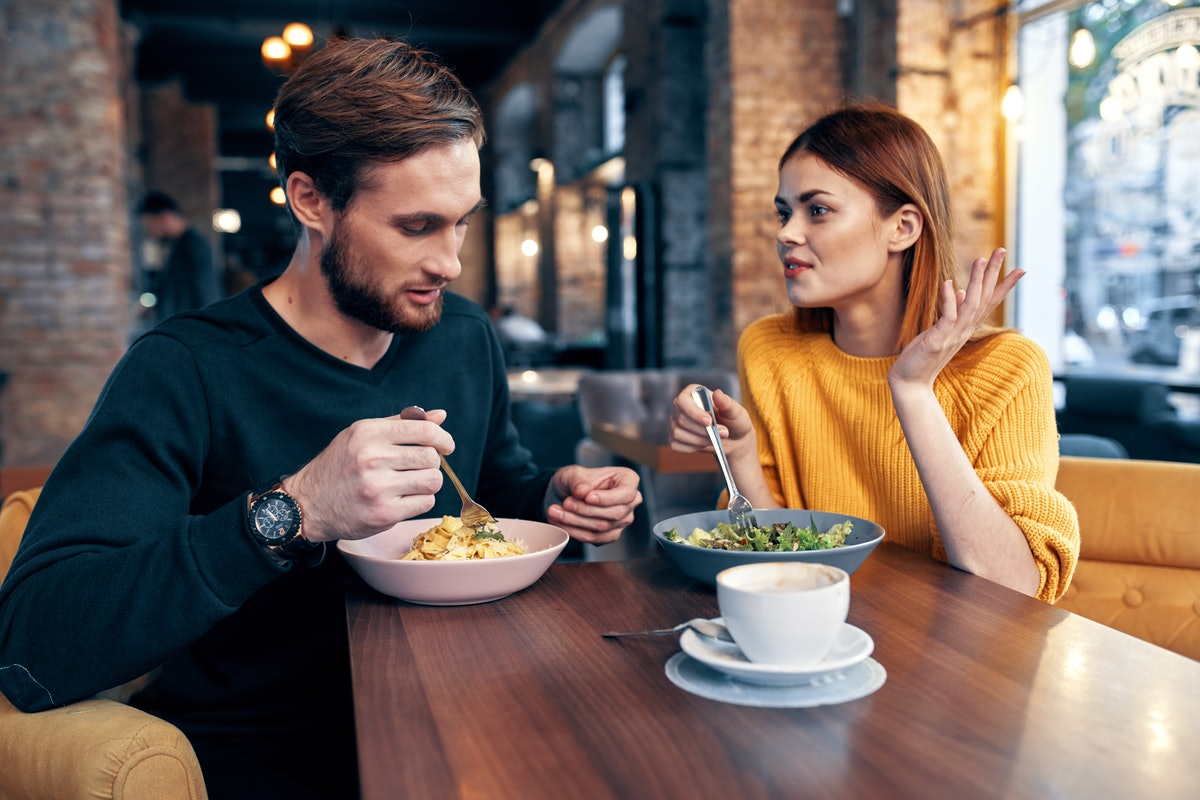 a man and a young woman in a yellow sweater are sitting at a table in a cafe