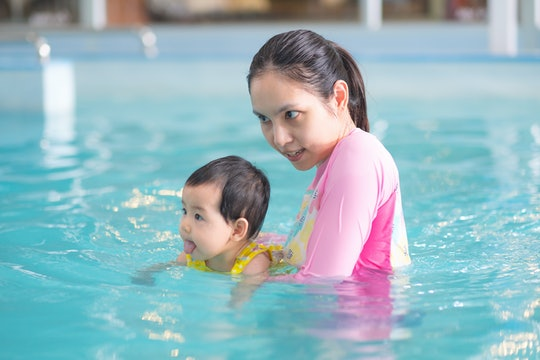 Mother and asian baby girl swimming in a pool, early development class for infants swimming. Baby sw...